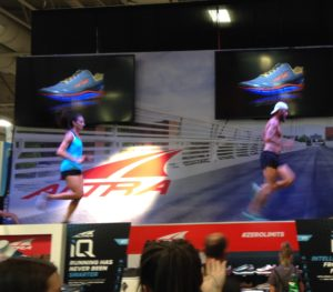 Altra booth featured elite athletes in action above the crowds